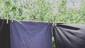 Ropa lavada limpia colgada en el alambre con la clavija de ropa y el fondo borroso de la naturaleza de la primavera en pueblo metrajes