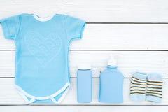 Ropa linda del bebé azul para el muchacho Mono, calcetines, cosméticos en el espacio de madera blanco de la copia de la opinión s Imagenes de archivo