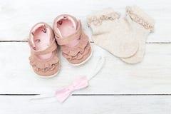 Ropa para el bebé y los accesorios en un backgro de madera blanco Imágenes de archivo libres de regalías