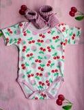 Ropa para los recién nacidos con las cerezas y botines del rosa del ` s del bebé en las ropas de cama con las cerezas Foto de archivo