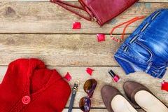 Ropa para mujer y accesorios del otoño: suéter rojo, vaqueros, bolso, gotas, gafas de sol, esmalte de uñas, zapatos, correa Imagen de archivo libre de regalías