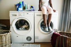 Ropa que espera adolescente joven de la muchacha para que se lavará de la lavadora Fotos de archivo
