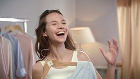 Ropa que intenta de la mujer joven en el guardarropa Mujer feliz que se divierte antes de partido almacen de video