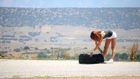 Ropa que lanza de la mujer joven de la maleta metrajes
