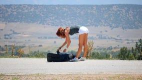 Ropa que lanza de la mujer joven de la maleta almacen de metraje de vídeo
