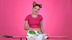 Ropa que plancha de la muchacha con un hierro en un tablero rosado Fondo rosado Cámara lenta metrajes