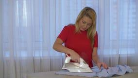 Ropa que plancha de la mujer en el tablero que plancha que se coloca de nuevo a ventana en el sitio casero almacen de metraje de vídeo