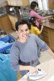 Ropa que plancha del hombre con la familia en cocina Imagen de archivo libre de regalías