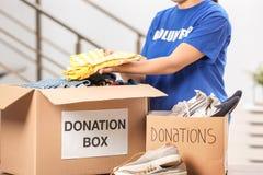 Ropa que pone voluntaria de la hembra en caja de la donación imágenes de archivo libres de regalías