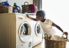 Ropa que se lava adolescente joven de la muchacha usando la lavadora Fotos de archivo