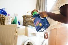 Ropa que se lava adolescente joven de la muchacha usando la lavadora Foto de archivo