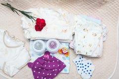 Ropa recién nacida del bebé con la botella Imágenes de archivo libres de regalías