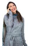 Ropa sonriente del invierno de la morenita que lleva bonita que tiene llamada de teléfono Imagen de archivo libre de regalías