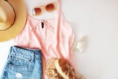 Ropa y accesorios de la mujer: top rosado, falda de los vaqueros, perfume, sandalias, gafas de sol, sombrero, lápiz labial en el  Imagenes de archivo