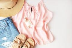 Ropa y accesorios de la mujer: top rosado, falda de los vaqueros, perfume, sandalias, gafas de sol, sombrero, lápiz labial en el  Imagen de archivo