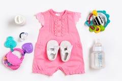 Ropa y accesorios del bebé en el fondo blanco Visión superior Imagen de archivo