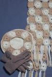 Ropa y accesorios del otoño Boina, guantes y bufanda hechos punto en un fondo gris Foto de archivo