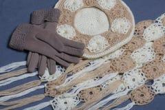 Ropa y accesorios del otoño Boina, guantes y bufanda hechos punto en un fondo gris Imagen de archivo