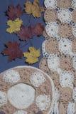 Ropa y accesorios del otoño E Asperjado con las hojas de otoño coloridas en un fondo gris Fotografía de archivo