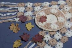 Ropa y accesorios del otoño E Asperjado con las hojas de otoño coloridas en un fondo gris Fotos de archivo libres de regalías