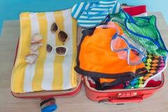 Ropa y accesorios del ` s de las mujeres en maleta negra Abra la maleta llena para viajar Foto de archivo libre de regalías