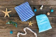 Ropa y accesorios del verano del ` s de las mujeres en viejo fondo de madera Fotos de archivo libres de regalías
