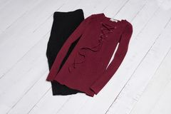 Ropa y accesorios Falda negra de Midi y suéter rojo con el cordón en los tablones de madera blancos del piso Endecha plana foto de archivo