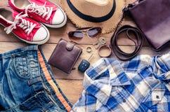 Ropa y accesorios para el viaje en el fondo de madera Fotos de archivo
