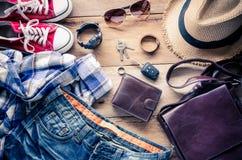 Ropa y accesorios para el viaje en el fondo de madera Foto de archivo libre de regalías