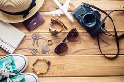 Ropa y accesorios para el viaje en el piso de madera Foto de archivo libre de regalías