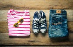 Ropa y accesorios para el viaje en el piso de madera Imágenes de archivo libres de regalías