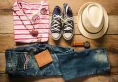 Ropa y accesorios para el viaje en el piso de madera Imagen de archivo libre de regalías