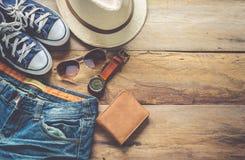 Ropa y accesorios para el viaje en el piso de madera Fotografía de archivo libre de regalías