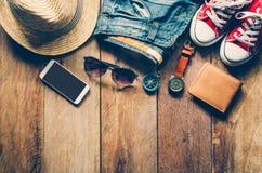 Ropa y accesorios para el viaje en piso de madera Imagen de archivo libre de regalías