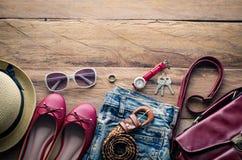 Ropa y accesorios para las mujeres, colocados en un piso de madera Imágenes de archivo libres de regalías