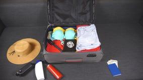 Ropa y cosas que llenan la maleta Preparaciones al viaje del verano Desgaste que embala y otros accesorios a empaquetar Planifica almacen de video