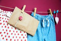 Ropa y mercancías del bebé que cuelgan en la cuerda para tender la ropa Imagen de archivo