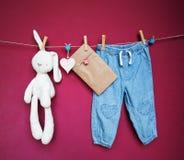 Ropa y mercancías del bebé que cuelgan en la cuerda para tender la ropa Fotografía de archivo