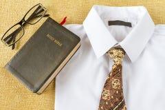 Ropa y Sagrada Biblia del estilo del hombre de negocios en casa Imagen de archivo libre de regalías