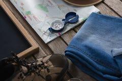 Ropas y accesorios que viajan en tablón de madera Fotos de archivo libres de regalías