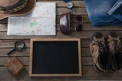 Ropas y accesorios que viajan en tablón de madera Imagen de archivo libre de regalías