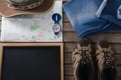 Ropas y accesorios que viajan en tablón de madera Imágenes de archivo libres de regalías