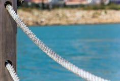 Rope поручни сделанные веревочки против голубого моря стоковые изображения