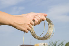 Rope. Shiny rope in hands on sky backgroung Royalty Free Stock Images