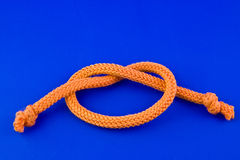 Rope. Part of orange rope isolated on blue background Royalty Free Stock Images