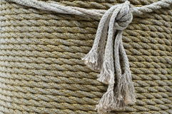 Rope. Abstract background. A rope is winded on a thick mast. Marine theme.Rope; mast of ship; intertwining filaments; thread; knot; abstract background Stock Image