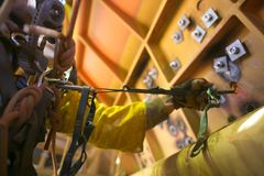 Rope access miner male hand working at height commencing clipping positioning safety hook against the wall to stopping body swingi royalty free stock photography