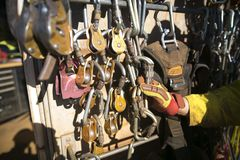 Rope access miner technician inspector hand inspecting safety check on descenders, locking carabiners hardware equipment stock photos