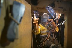 Rope access welder commencing welding in confined space. Rope access welder wearing fully safety uniform fall protection helmet, welding glove harness stock images