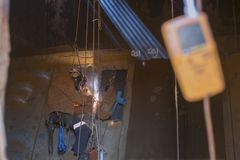 Rope access welder wearing safety equipment, harness helmet doing hot work, welding in confined space which have blurry gas test d. Etector on the foreground at royalty free stock images